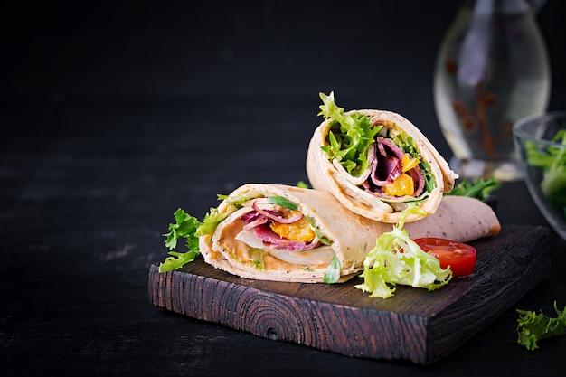 Świeża tortilla zawija się z szynką wołową i świeżymi warzywami na desce. burrito z wołowiną. kuchnia meksykańska. skopiuj miejsce