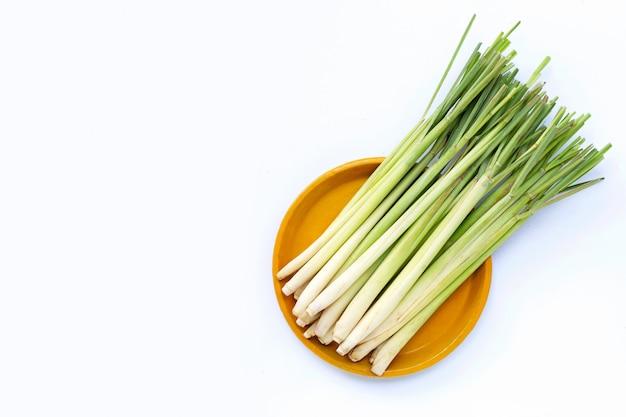Świeża trawa cytrynowa na żółtym talerzu na białym tle.
