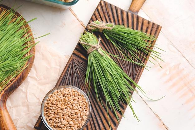 Świeża trawa pszeniczna i nasiona w misce na jasnej powierzchni