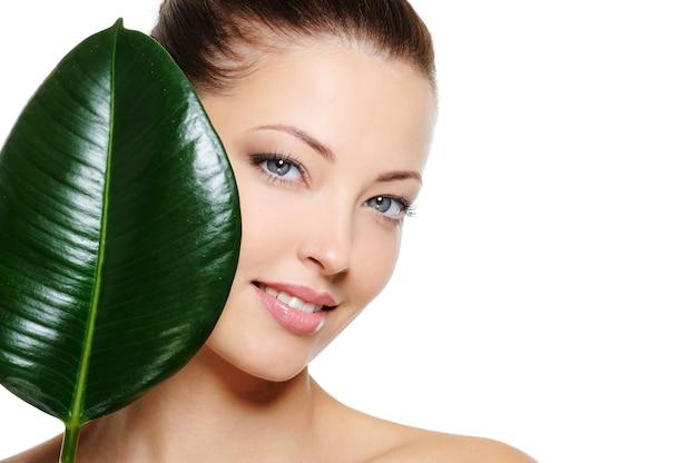 Świeża twarz kobiety z wesołym uśmiechem i dużym zielonym liściem na białych deseniach