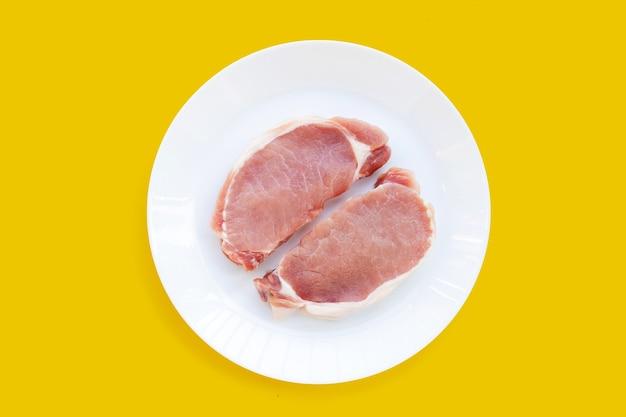 Świeża wieprzowina w białej płytce na żółtym tle.