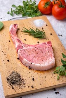 Świeża wieprzowina z przyprawami, rozmarynem i czarnym pieprzem na drewnianej desce do krojenia