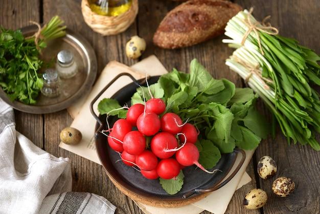 Świeża wiosenna rzodkiew z dzikim czosnkiem pietruszką i jajkami przepiórczymi na drewnianej powierzchni. składniki na sałatkę.