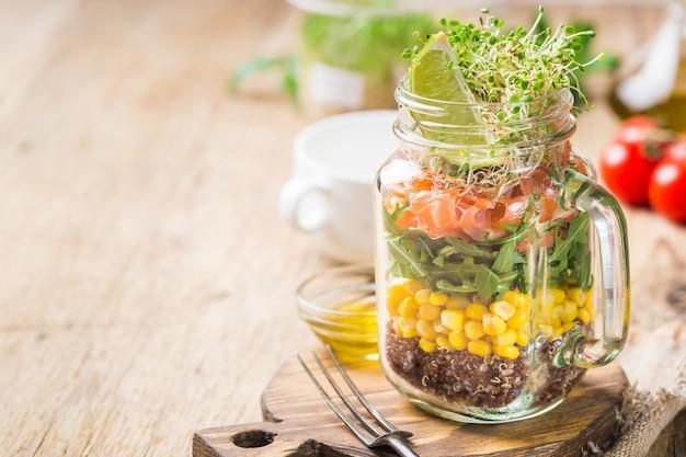 Świeża wiosenna sałatka z łososiem, komosą ryżową, rukolą, rzeżuchą i kukurydzą w słoiku.