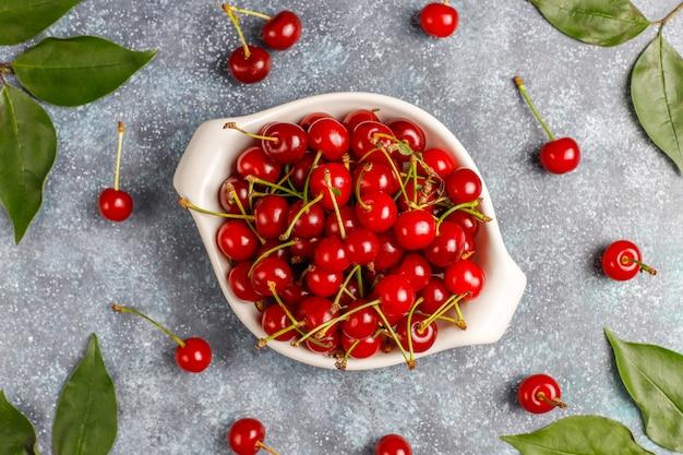 Świeża wiśnia na talerzu na szarym stołowym odgórnym widoku