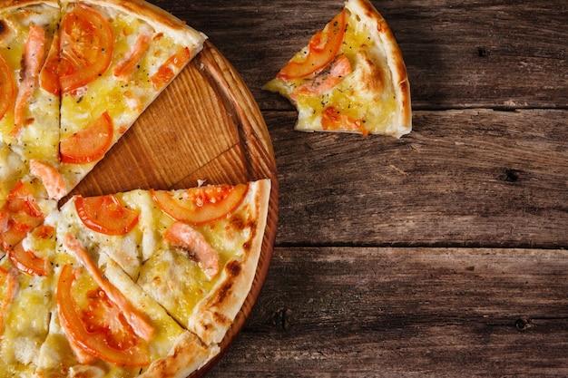 Świeża włoska pizza z pokrojoną w plasterki podawana na rustykalnym drewnianym stole, leżała płasko. kalorie, niezdrowe jedzenie, złe nawyki. ciemne drewniane tło z wolnym miejscem na tekst.
