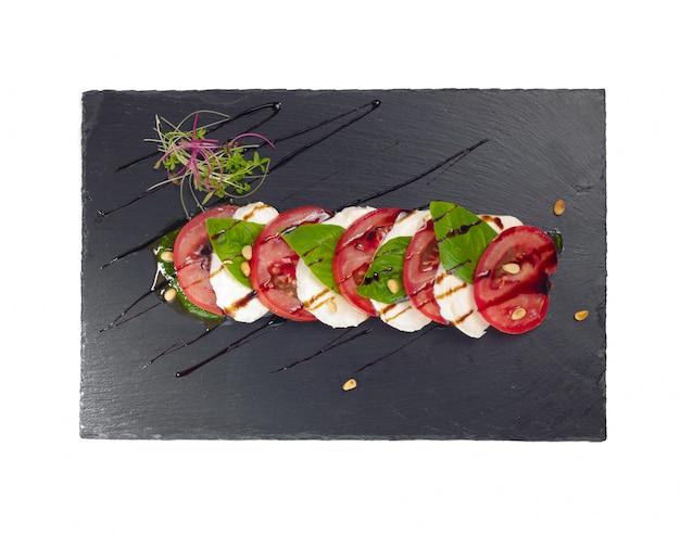 Świeża włoska sałatka caprese z mozzarellą i pomidorami na ciemnym talerzu