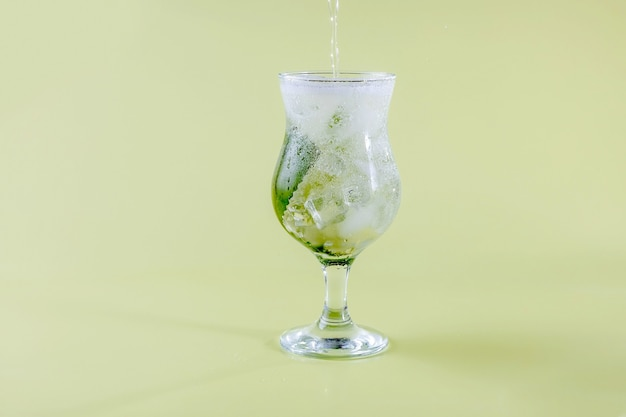 Świeża woda seltzer wlewa się do szklanki z miętą i lodem