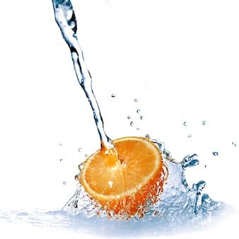 Świeża woda spada na pomarańczowy na białym tle