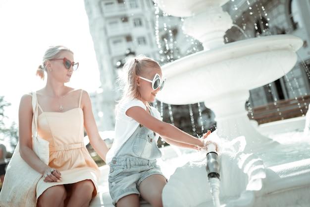 Świeża woda. uśmiechnięta dziewczynka myje ręce w fontannie, siedząc przed swoją poważną matką.