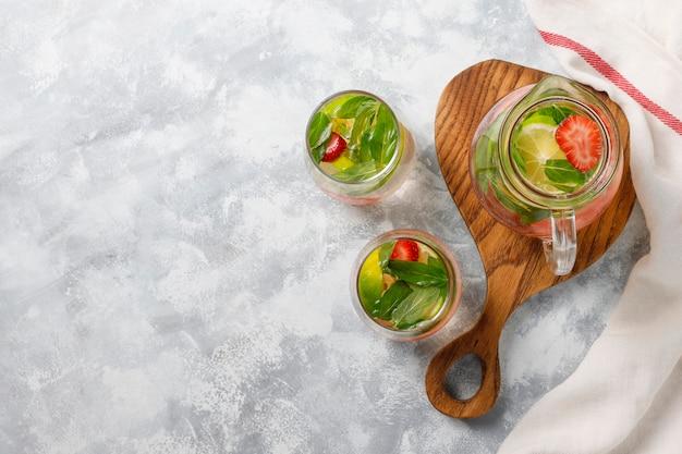 Świeża woda z limonką, truskawkami i miętą, koktajl, napój detoksykacyjny, lemoniada. letnie drinki. pojęcie opieki zdrowotnej.