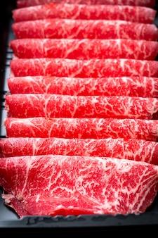 Świeża wołowina surowa w plasterkach o marmurkowej fakturze