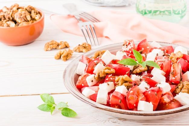Świeża zakąska pomidory, ser feta, orzechy włoskie, siemię lniane i nasiona sezamu w talerzu na drewnianym stole
