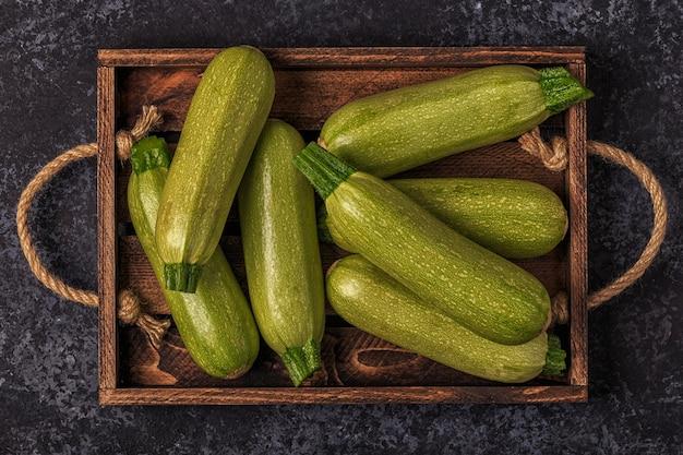 Świeża zdrowa cukinia zielona cukinia w brązowym drewnianym pudełku