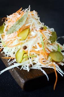 Świeża zdrowa sałatka - kapusta, marchewka, marynata. coleslaw na drewnianej desce na lekkiej ścianie. warzywa do fermentacji, do długiej fermentacji. asortyment świeżych warzyw. koncepcja zdrowej żywności.