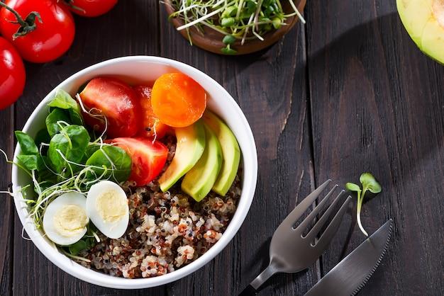 Świeża zdrowa sałatka z komosą ryżową, pomidorami koktajlowymi i mieszaną zielenią, awokado, jajkiem i mikro zieleniną na drewnie