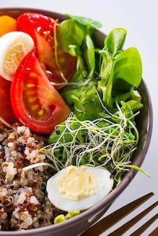 Świeża zdrowa sałatka z komosą ryżową, pomidorami koktajlowymi i mieszaną zielenią, awokado, jajkiem i mikro zieleniną na marmurze