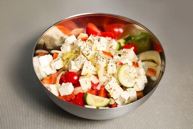 Świeża zdrowa sałatka z pomidorów, ogórków, cebuli i sera. kuchnia grecka, potrawy dietetyczne, odchudzanie.