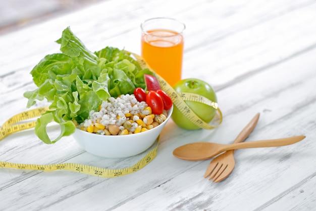 Świeża zdrowa sałatka z taśmy miarą na stole. koncepcja fitness i zdrowia.