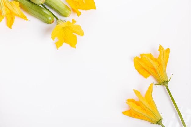 Świeża zielona cukinia z kwiatem i liśćmi na białym tle. pojęcie zdrowego odżywiania, żywności dla niemowląt, weganizmu, wegetarianizmu, surowej żywności. widok z góry, układ płaski. skopiuj miejsce.