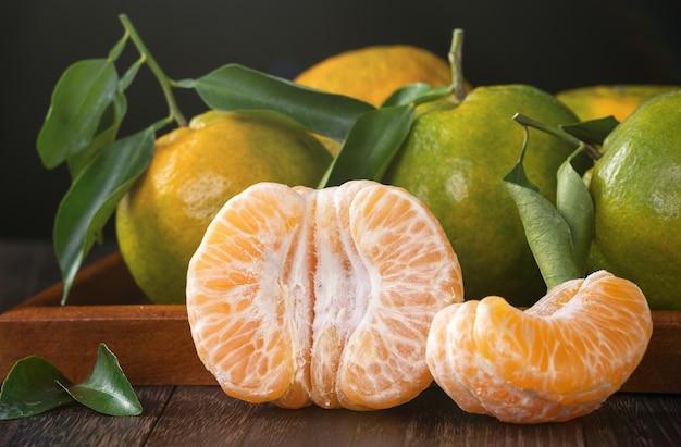 Świeża zielona mandarynka z liśćmi na tle ciemny drewniany stół