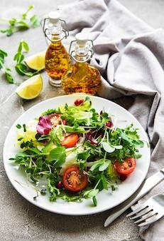 Świeża zielona miska sałatki mieszanej z pomidorami i zielonymi liśćmi na betonowym stole. zdrowa żywność, widok z góry.