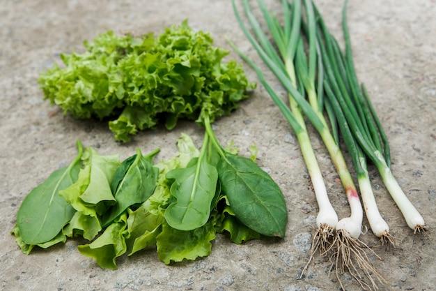 Świeża zielona sałata, szpinak, zielona cebula z ogrodowego łóżka na kamiennej ścianie. ekologiczna żywność i koncepcja zdrowego stylu życia.