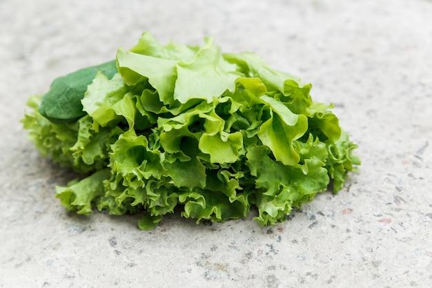 Świeża zielona sałata z łóżka ogrodowego na kamiennej ścianie. ekologiczna żywność i koncepcja zdrowego stylu życia