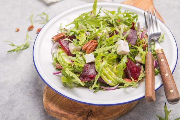 Świeża zielona sałatka organiczna z rukolą, plastry buraków, ser feta, orzechy, jabłko na białym talerzu, widok z góry. zdrowe odżywianie, pojęcie diety