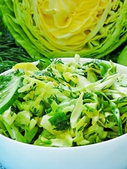 Świeża zielona sałatka wegetariańska z młodą kapustą, ogórkiem i zieleniną