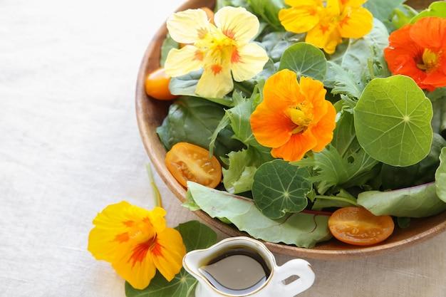Świeża zielona sałatka z jadalnymi kwiatami nasturcja w drewnianym porci naczyniu