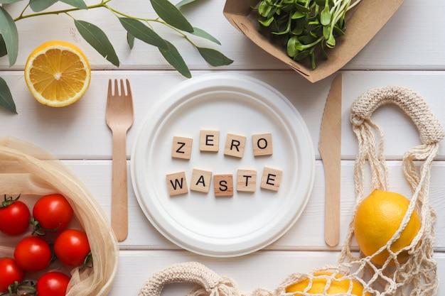 Świeża zielonka, pomidory, cytryny i napis zero waste z drewnianych liter