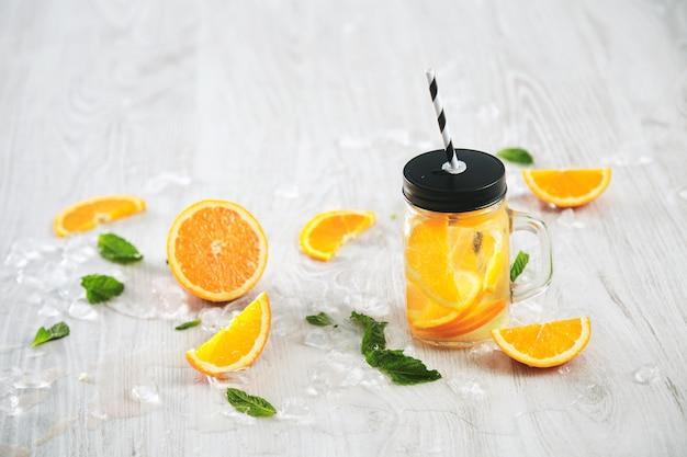 Świeża zimna letnia lemoniada z cytrusów i wody gazowanej w rustykalnym słoiku ze słomką w paski na drewnianym stole.