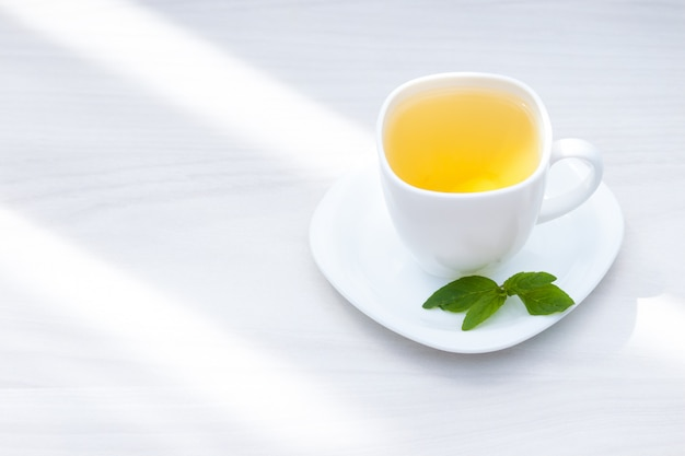 Świeża ziołowa nowa herbata na białym drewnianym tle. leżał płasko, kopia przestrzeń.