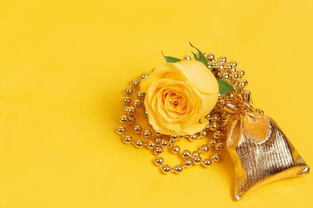 Świeża żółta róża ozdobiona koralikami oraz torebka prezentowa na żółtym tle.