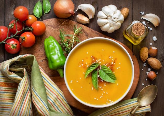 Świeża zupa dyniowa i warzywa na brązowy drewniany stół widok z góry