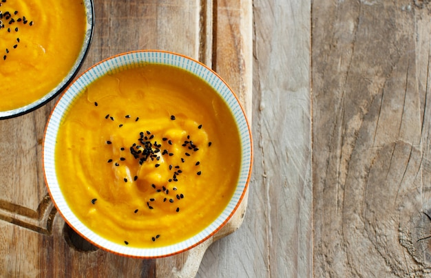 Świeża zupa dyniowa w dwóch miseczkach na drewnianym stole