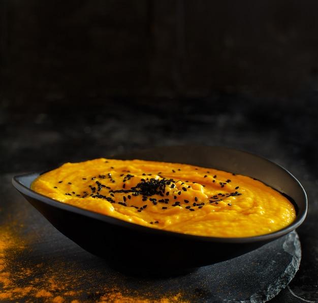 Świeża zupa dyniowa w misce na ciemnym tle