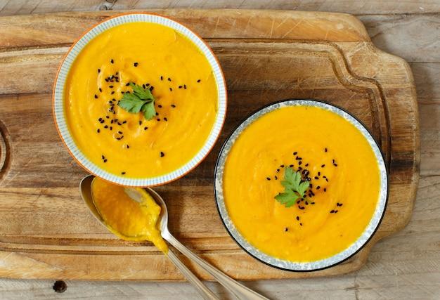 Świeża zupa dyniowa w miseczkach na drewnianym stole