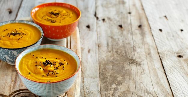 Świeża zupa dyniowa w trzech miseczkach na drewnianym stole