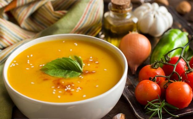 Świeża zupa dyniowa z łyżką i warzywami na brązowy drewniany stół z bliska