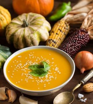 Świeża zupa dyniowa z łyżką i warzywami