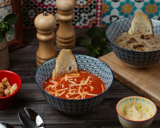 Świeża zupa pomidorowa z drobno posiekanym parmezanem i kromką chleba w niebieskiej misce