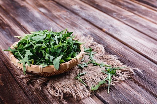 Świeża żywność, zdrowe życie. zielony arugula słuzyć w pucharze na nieociosanym tle