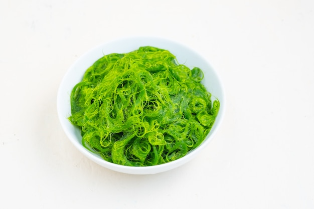 Świeże algi w pucharze na białym tle kosmos kopii .asia jedzenie naturalne jedzenie