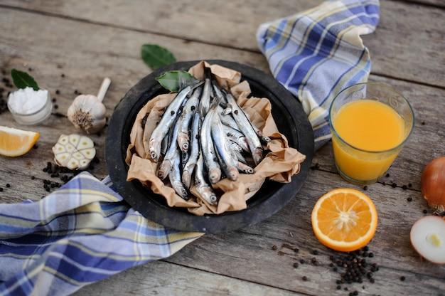 Świeże anchois na talerzu na papierze do pieczenia ze świeżym sokiem pomarańczowym, czosnkiem, cebulą i cytryną dookoła na niebieskiej serwetce na drewnianym stole