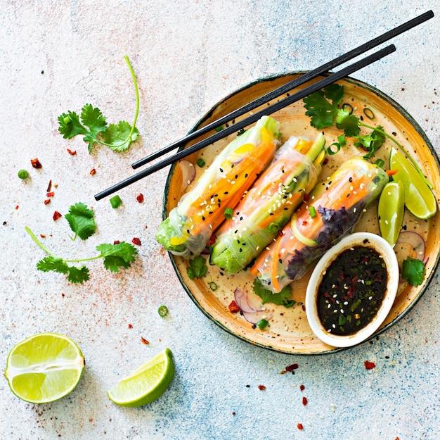 Świeże azjatyckie przekąski sajgonki (nem) wykonane z papieru ryżowego oraz surowych warzyw i ziół z ostrym sosem na jasnoniebieskim tle.