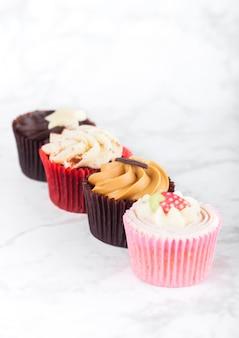 Świeże babeczki babeczki z karmelem i czekoladą, truskawkami i toffi na marmurowej desce