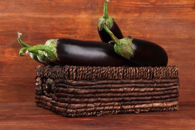Świeże bakłażany w wiklinowym koszu na stole na drewnianym tle
