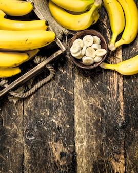 Świeże banany na starej tacy. na drewnianym stole.